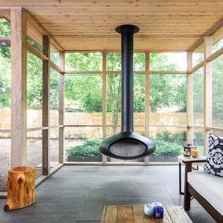 Idées déco pour une véranda moderne de taille moyenne avec un sol en carrelage de porcelaine, cheminée suspendue, un plafond standard et un sol gris.