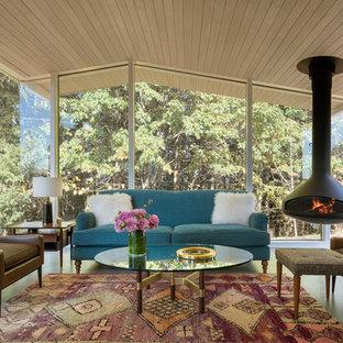 Cette image montre une véranda rustique avec béton au sol, cheminée suspendue et un plafond standard.