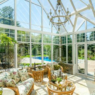 Foto di una veranda tradizionale di medie dimensioni con pavimento in travertino e soffitto in vetro