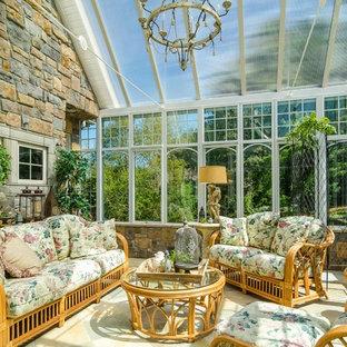 Cette photo montre une véranda chic de taille moyenne avec un sol en travertin et un plafond en verre.