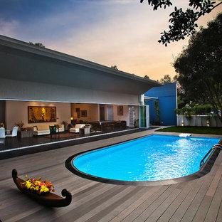 Großer Moderner Pool hinter dem Haus in Nierenform mit Dielen in Bangalore