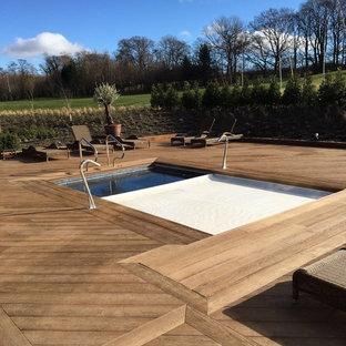 Modelo de piscina elevada, escandinava, en patio trasero, con entablado