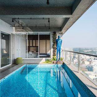 Diseño de piscina alargada, urbana, interior y rectangular, con losas de hormigón