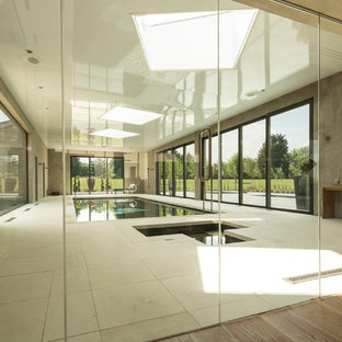 Large modern indoor rectangular lengths swimming pool in Hampshire with a hot tub and natural stone paving.