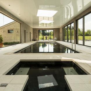 Ispirazione per una grande piscina coperta monocorsia minimalista rettangolare con una dépendance a bordo piscina e pavimentazioni in pietra naturale