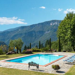 Esempio di una grande piscina mediterranea rettangolare con pavimentazioni in pietra naturale