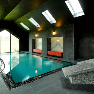 This is an example of a medium sized contemporary indoor rectangular swimming pool in Other with a pool house and tiled flooring.
