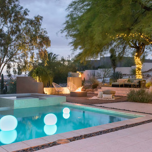 This is an example of a large contemporary backyard rectangular infinity pool in Phoenix with a hot tub and decomposed granite.
