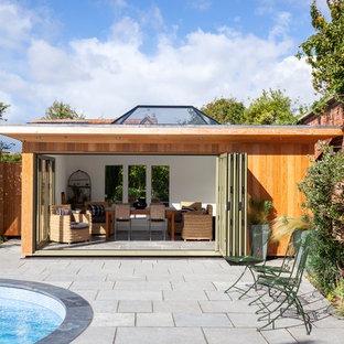 This is an example of a medium sized contemporary back kidney-shaped swimming pool in Wiltshire with a pool house and natural stone paving.