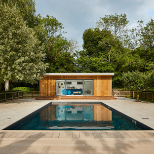 Contemporary back rectangular swimming pool in Essex with a pool house and decking.