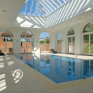This is an example of a medium sized classic indoor rectangular lengths swimming pool in Other with a pool house and tiled flooring.