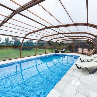 Bild på en mellanstor funkis inomhus, rektangulär träningspool, med kakelplattor