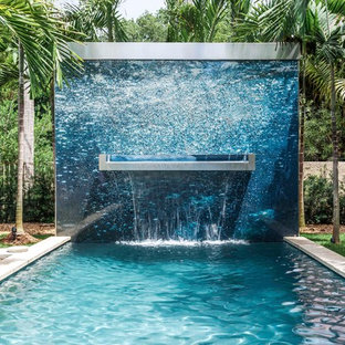 Photo of a contemporary back rectangular swimming pool in London with a water feature.