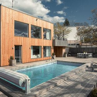 ストックホルムの長方形北欧スタイルのおしゃれなプール (デッキ材舗装) の写真