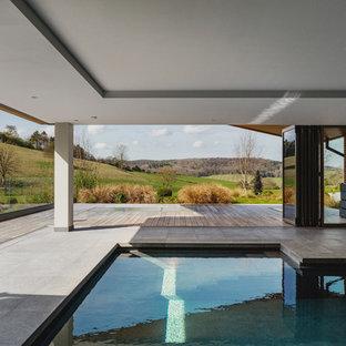 Ejemplo de piscina actual, de tamaño medio, interior y en forma de L, con losas de hormigón