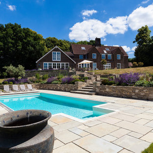 Photo of a medium sized classic back rectangular swimming pool in Sussex with natural stone paving.