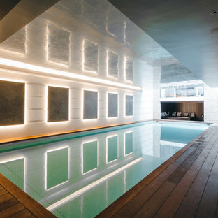 Large Contemporary Indoor Rectangular Swimming Pool In London With A Pool  House And Decking.