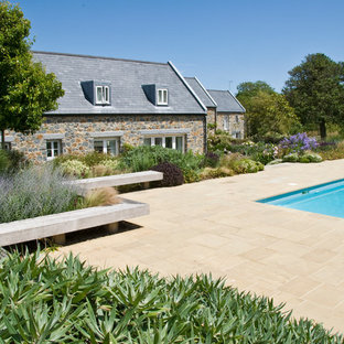 Inspiration for a large rural back rectangular lengths swimming pool in Channel Islands with natural stone paving.