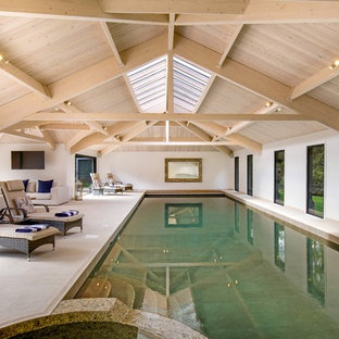 Photo of a contemporary indoor rectangular lengths swimming pool in London with a pool house.