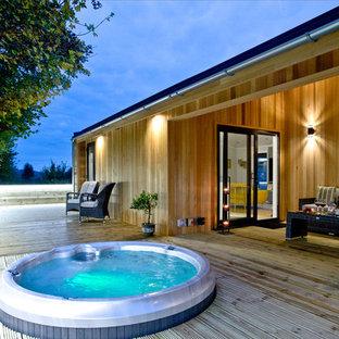 Diseño de piscinas y jacuzzis costeros, grandes, redondeados, en azotea, con entablado