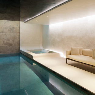 Large modern indoor rectangular lengths swimming pool in London with a hot tub.