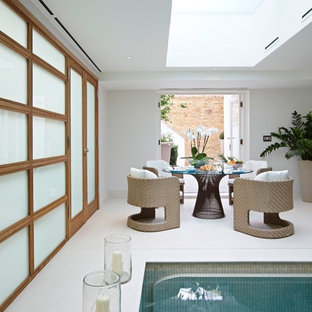 This is an example of a contemporary indoor swimming pool in London with a pool house.