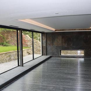 Modelo de casa de la piscina y piscina elevada, actual, de tamaño medio, rectangular, en patio trasero, con granito descompuesto
