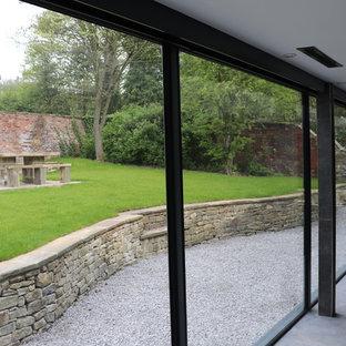 Modelo de casa de la piscina y piscina elevada, contemporánea, de tamaño medio, rectangular, en patio trasero, con granito descompuesto