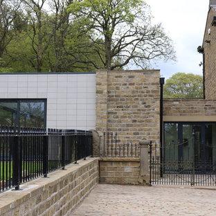 Ejemplo de casa de la piscina y piscina elevada, actual, de tamaño medio, rectangular, en patio trasero, con granito descompuesto
