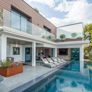 Idée de décoration pour une grand piscine à débordement et arrière design rectangle avec du carrelage.