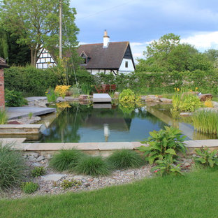 Large rural back rectangular natural swimming pool in Other with a water feature and natural stone paving.