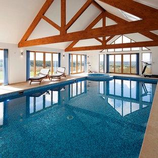 Ejemplo de piscina elevada, minimalista, de tamaño medio, interior y rectangular, con suelo de baldosas