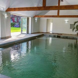 Foto di una grande piscina monocorsia contemporanea rettangolare dietro casa con una dépendance a bordo piscina e pavimentazioni in pietra naturale