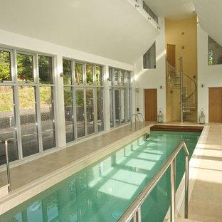 Imagen de casa de la piscina y piscina actual, rectangular y interior, con suelo de baldosas
