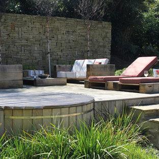 Ejemplo de piscinas y jacuzzis campestres, grandes, redondeados, en patio trasero, con entablado