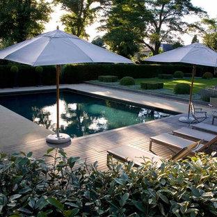 Ejemplo de piscina campestre, de tamaño medio, rectangular, en patio trasero, con adoquines de piedra natural