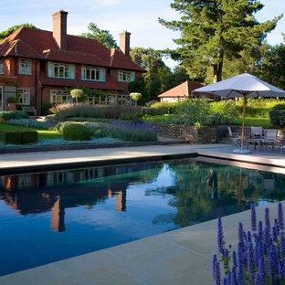 サセックスの中サイズの長方形カントリー風おしゃれな裏庭プール (天然石敷き) の写真