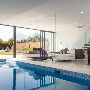Imagen de piscina contemporánea, rectangular y interior, con suelo de baldosas
