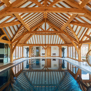 This is an example of a contemporary indoor rectangular swimming pool in Other with a pool house.