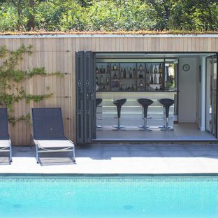 Contemporary swimming pool in Dorset with a pool house.