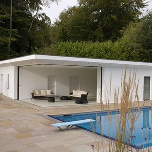 Photo of a modern rectangular swimming pool in London with a pool house.