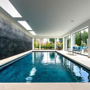 Diseño de piscina alargada, actual, de tamaño medio, interior y rectangular, con adoquines de piedra natural