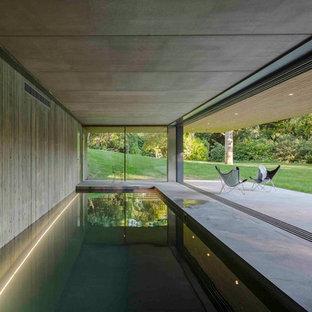 Diseño de piscina grande, rectangular y interior, con losas de hormigón