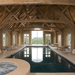 Inspiration for a rustic indoor rectangular swimming pool in West Midlands with a pool house and natural stone paving.