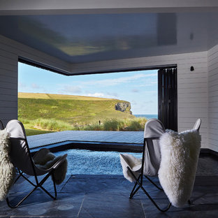 Photo of a small contemporary indoor custom shaped swimming pool in Cornwall with natural stone paving and a hot tub.
