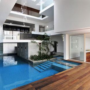 Diseño de piscina actual, grande, interior y en forma de L, con entablado