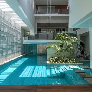 Idée de décoration pour une grande piscine intérieure design sur mesure.