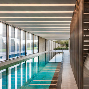 Photo of a contemporary indoor rectangular swimming pool in London with concrete slabs.