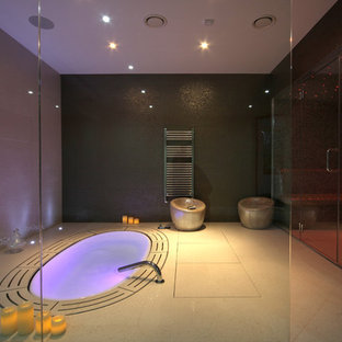 This is an example of a medium sized eclectic round swimming pool in Surrey with a hot tub.