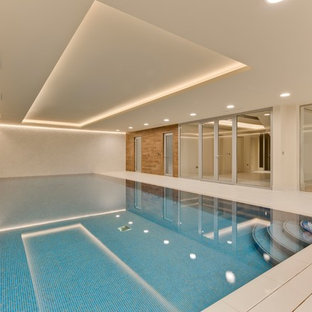 Photo of a large contemporary indoor rectangular lengths swimming pool in Surrey with tiled flooring.